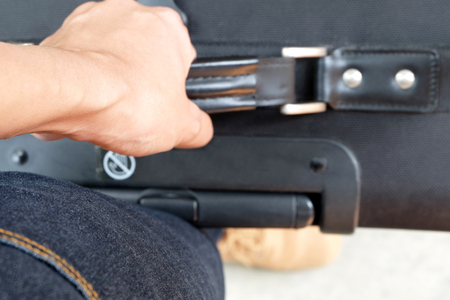 Tendons (selected focus) at wrist while carrying a black baggage with a brown boot and jeans