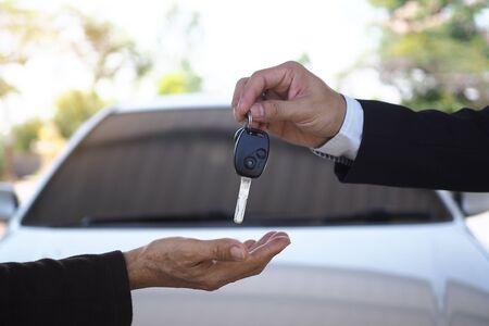 Photo pour The car salesman and the key to the new owner. - image libre de droit