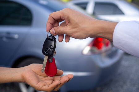 Photo pour Businessman handing over gives the car key for rental or sell to the customer on car background. salesman receiving money and giving car`s key to customer after sign agreement contract. - image libre de droit