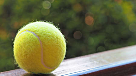 Photo pour Close up tennis ball on wooden floor with green background. Tennis sports background. - image libre de droit