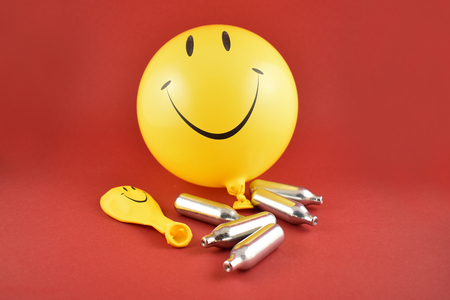 Foto de Laughing gas bombs stock images. Laughing gas balloons. Happy emoji balloon. Smiley inflatable balloon isolated on a red background. Laughing party balloon. Nitrous oxide bulbs - Imagen libre de derechos