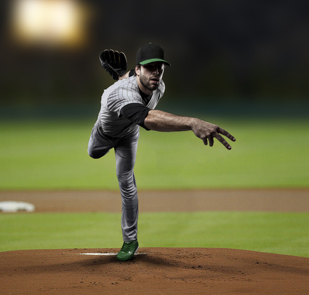 Pitcher Baseball Player on a Green Uniform on baseball Stadium.の写真素材