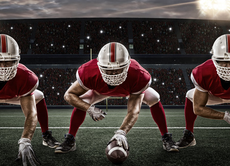 Photo for Football Players with a red uniform on the scrimmage line, on a stadium. - Royalty Free Image