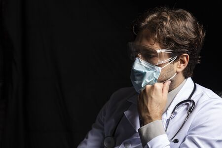 Photo pour male doctor wearing a mask and goggles, tired of working with covid-19 on a black background. - image libre de droit