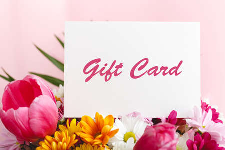 Photo pour Gift card in flowers bouquet on pink background. Gift card present coupon for woman. Surprise voucher for Mothers Day, Happy Birthday or anniversary for wife, mother day, daughter or granny - image libre de droit