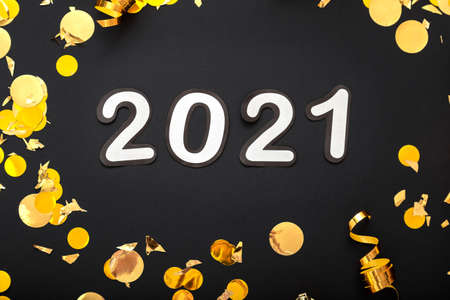 Photo pour 2021 white numbers text lettering in golden confetti, Christmas festive decor frame on black background. Happy New year event composition. Close up. - image libre de droit