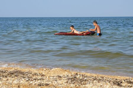 Boys bathe in the sea on an air mattress close to the shore. Children in the sea with a water mattress. Concept: safe rest for children in the water.