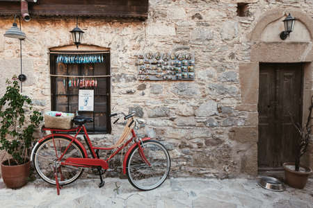 Photo pour Vintage red bicycle in front of a stone building in Datca, Turkey - image libre de droit