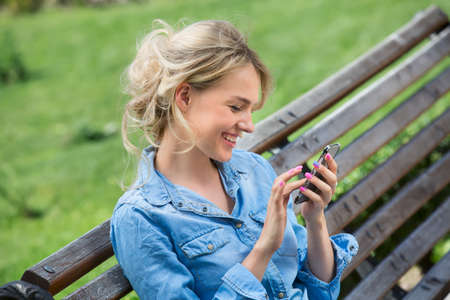 Cute blonde in a bright blue denim shirt emotionally talking on a cell phone.