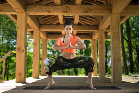 Beautiful girl does sumo squats on the black yoga mat on the wooden terrace on the nature background. She stands on the toes and holds her palms  together. She looks into the camera with a smile. She wears orange t-shirt and the wide olive pants with imag