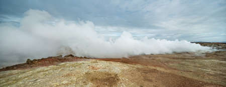 Geothermal geyser is steaming on the background of the cloudy sky in Iceland. Panoramic. Horizontal.