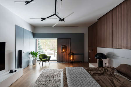 Modern bedroom with white walls and a parquet with a carpet on the floor. There is a bed with a brown linens and a gray plaid, black lamp on a stand, wooden lockers, luminous bulb lamps, armchair.