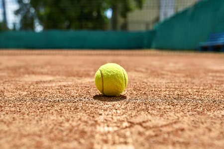 Yellow tennis ball on the ground on the court outdoors. Sun shines on it. Closeup. Horizontal.