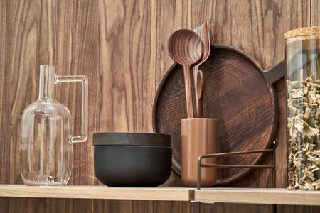 Photo pour Wooden shelves with wood and ceramic utensil and glass jar and jug on the textured wall background. Closeup horizontal photo. - image libre de droit