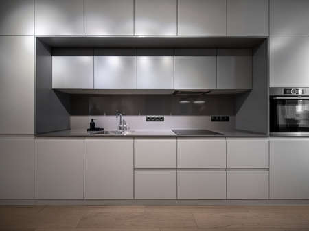 Photo pour Beautiful illuminated modern gray kitchen with a parquet on the floor. There are lockers and drawers, sink with a chrome faucet, black dispenser, stove, oven, power sockets. Horizontal. - image libre de droit