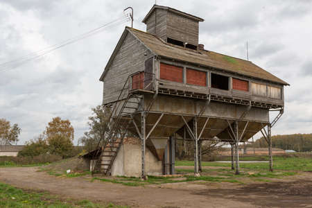 old grain dryer on the background of the autumn mud in Russia
