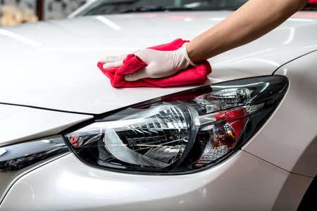 Foto de Car polishing series : Worker cleaning white car - Imagen libre de derechos
