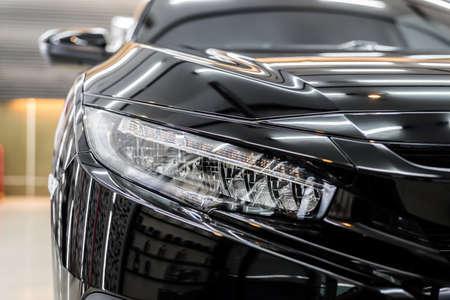 Foto de Car detailing series : Closeup of clean headlights of black car - Imagen libre de derechos