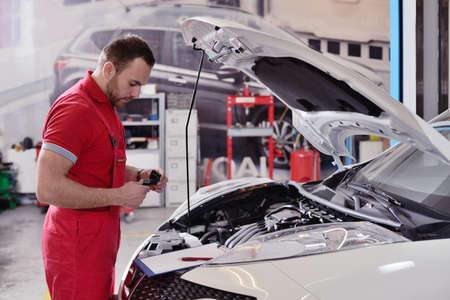 Photo pour Man working in a garage repairing car - image libre de droit