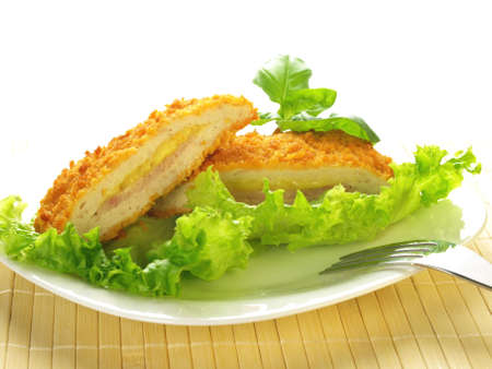 Cordon blue served on a plate with salad and basil leaves