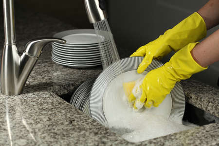 Closeup of washing a plates with protective gloves