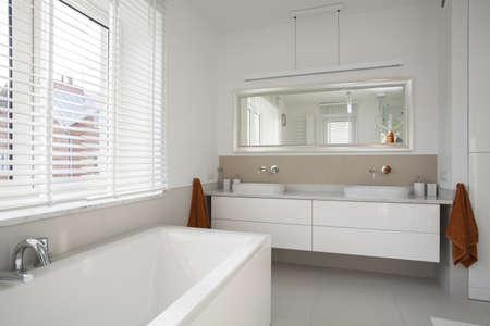 Interior of spacious, plain and white bathroom