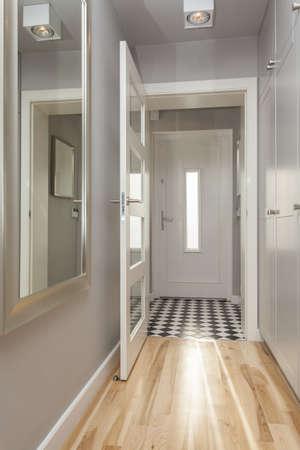 Bright corridor with open door in modern house