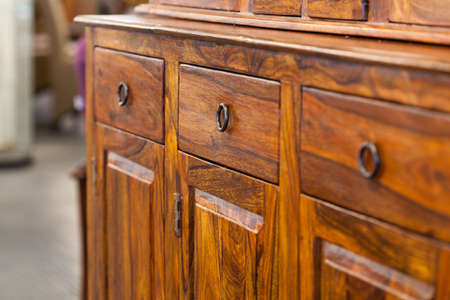 A closeup od a dark brown wooden cabinet with drawers