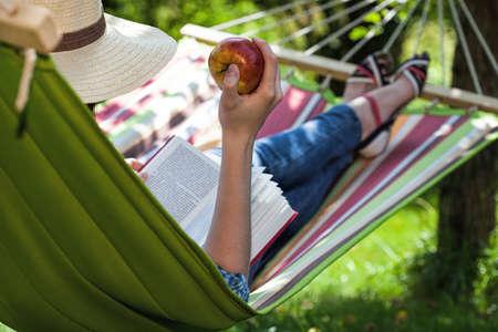 A reader having a snack on a hammock