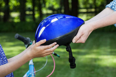 Close up of bicycle helmet held by two people