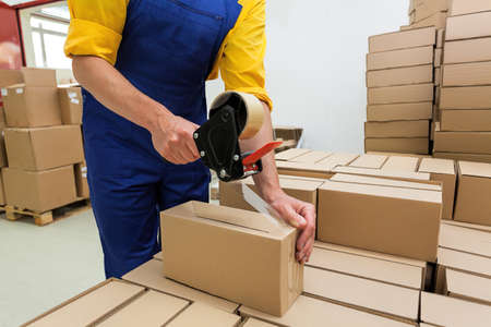 Factory worker with packing tape gun dispenser finishing a delivery