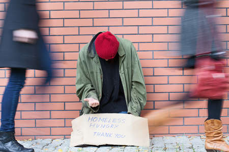 Homeless man sitting on a street passed by people