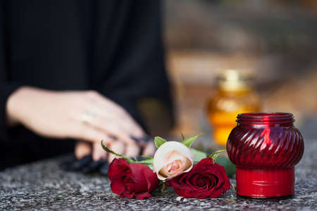 Woman in mourning arranging flowers and candles on the gravestone