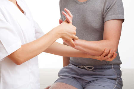 Female physiotherapist examining and massaging a hand