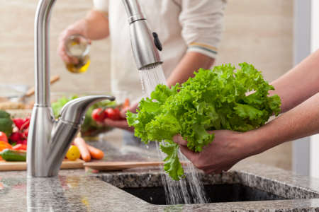 Washing fresh vegetables for a salad with an alive oil