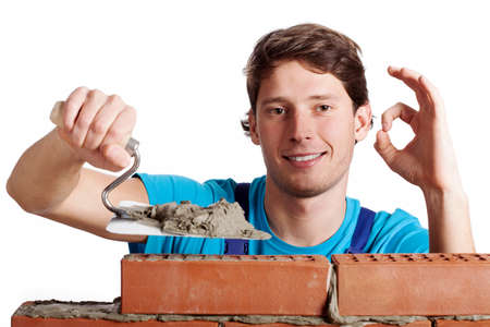 Happy man with putty knife building a brick wall
