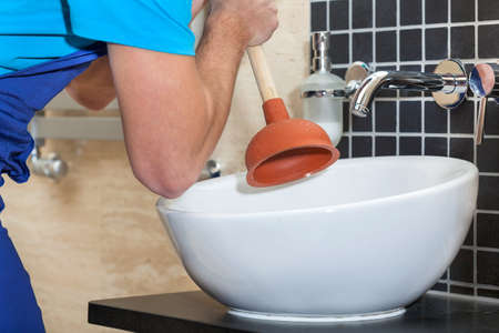Plumber with rubber plunger in a bathroom
