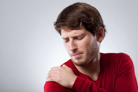 Young man is suffering from shoulder ache