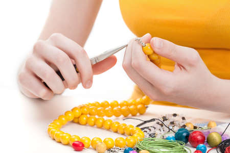 A woman making a wooden yellow bead necklace