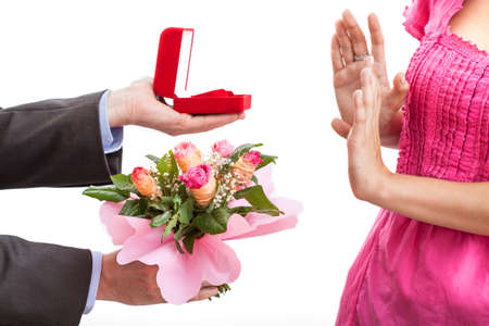 A man proposing with a ring and flowers and a woman rejecting