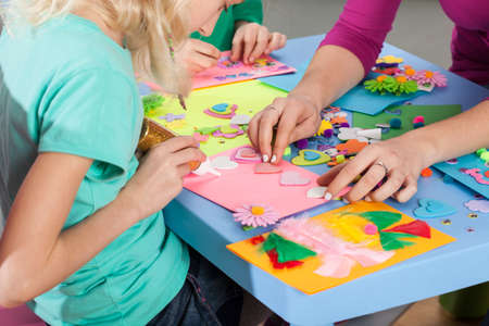 Children making decorations on colorful paper with art teacher