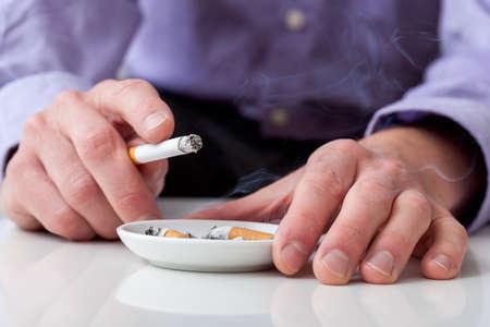 Man smoking cigarette and using an ashtray