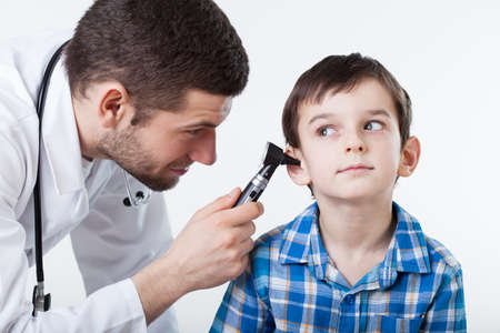 Physician performing ear examination during a visit
