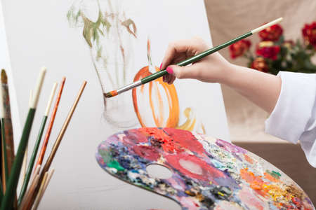 A closeup of an artist with a brush painting a picture