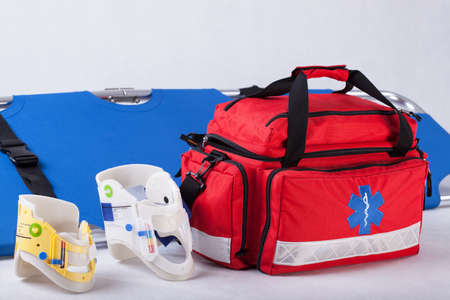 Rescue bag, cervical collars and stretcher on white background