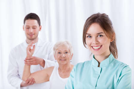 Smiling therapist standing in front of exercising elderly patient