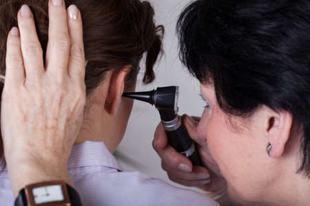 A closeup of a doctor examining her patient's ear