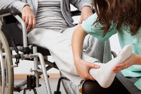 Disabled person during rehabilitation with her nurse