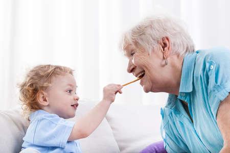 Grandson and his grandma eating together, horizontal