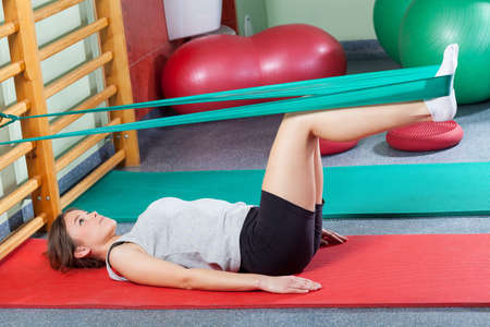 Girl lying on exercise mat and stretching legs with elastic band